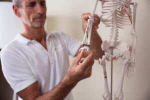 Roland Liebscher-Bracht is holding the arm of a skeleton to show how to treat carpal tunnel syndrome.