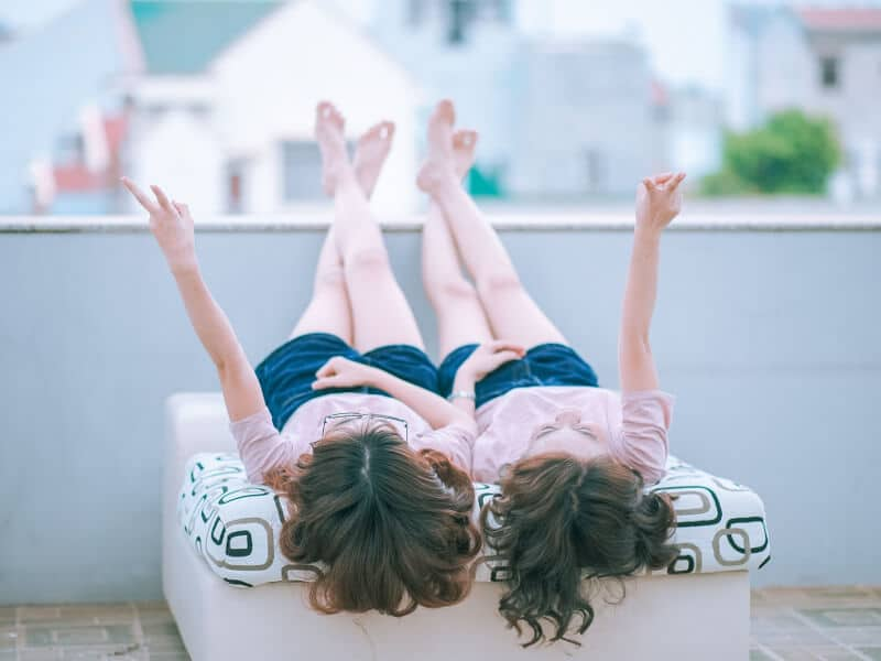 A pair of girls lying on their backs, mirroring their actions.