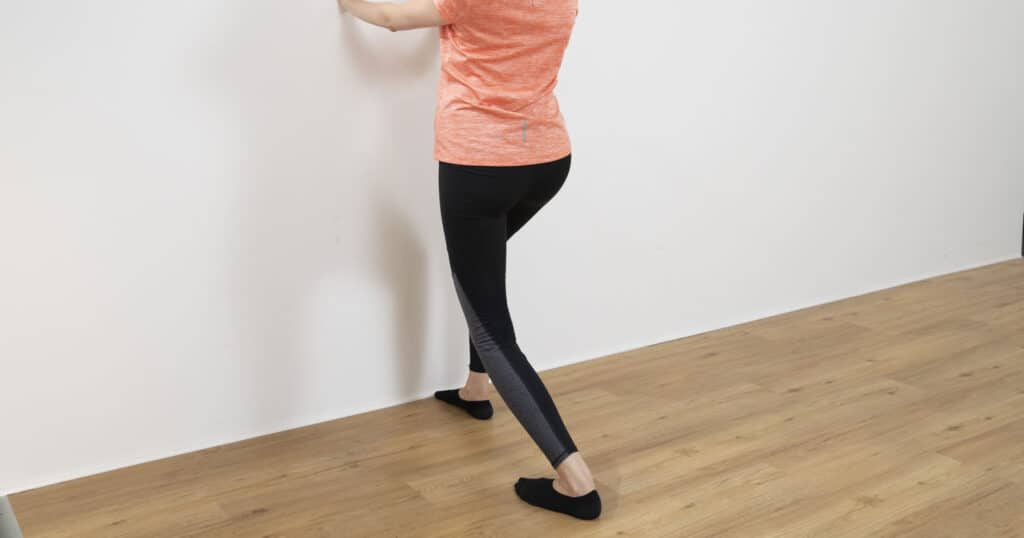 A woman is stretching her legs to get rid of hip pain