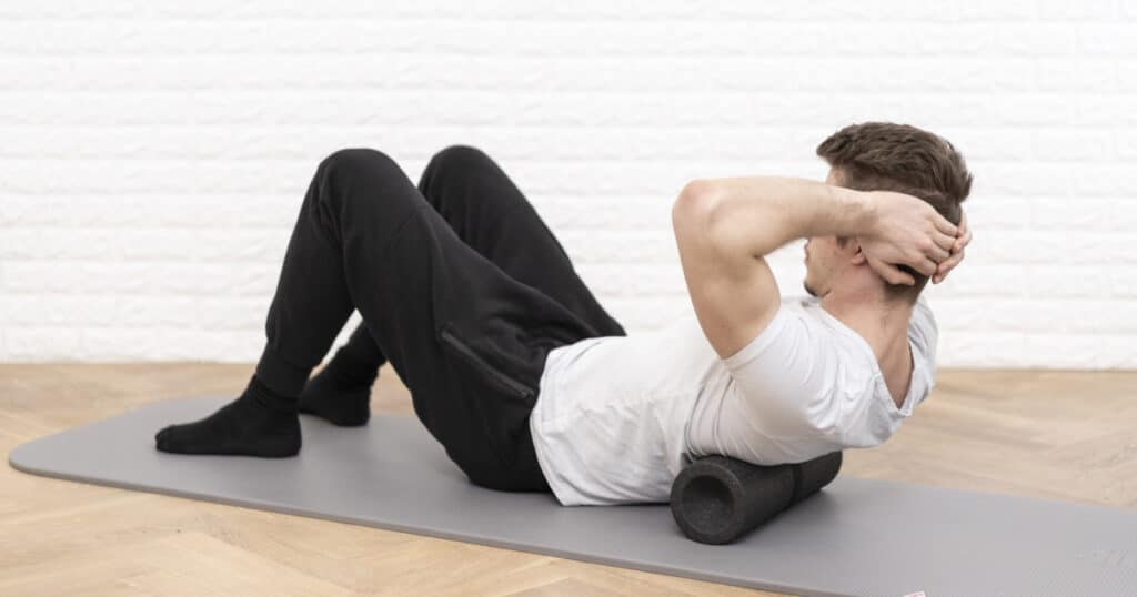 A man is using a fascia foam roll to ease the tension in his back