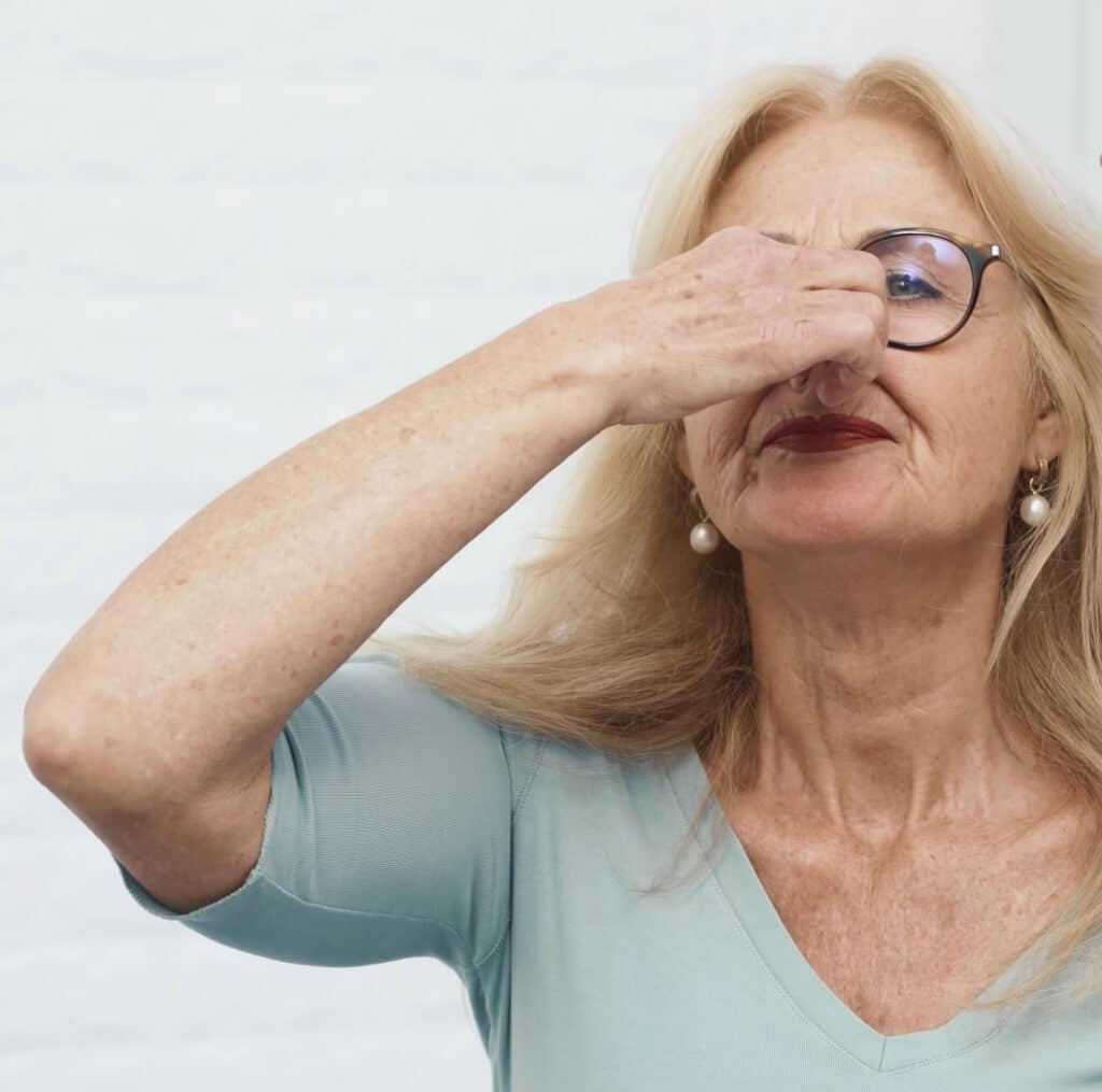 A woman is pinching her nose.