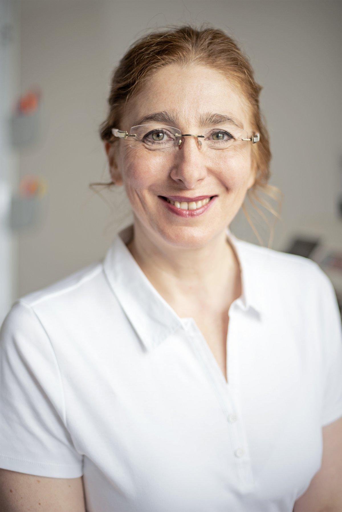 Auf dem Foto lacht Aleksandra Traub in die Kamera. Sie trägt ihre braunen Haare als Zopf und trägt eine randlose Brille. Weiterhin trägt sie ein weißes Polo T-Shirt.