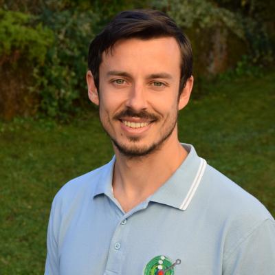 Das Foto zeigt den Physiotherapeuten Alexander Steif auf Ebensee vor einem grünen Naturhintergrund. Er hat dunkelbraune Haare und einen Schnauzer sowie einen Dreitagebart. Auf dem Foto trägt er ein hellblaues Polo T-Shirt.