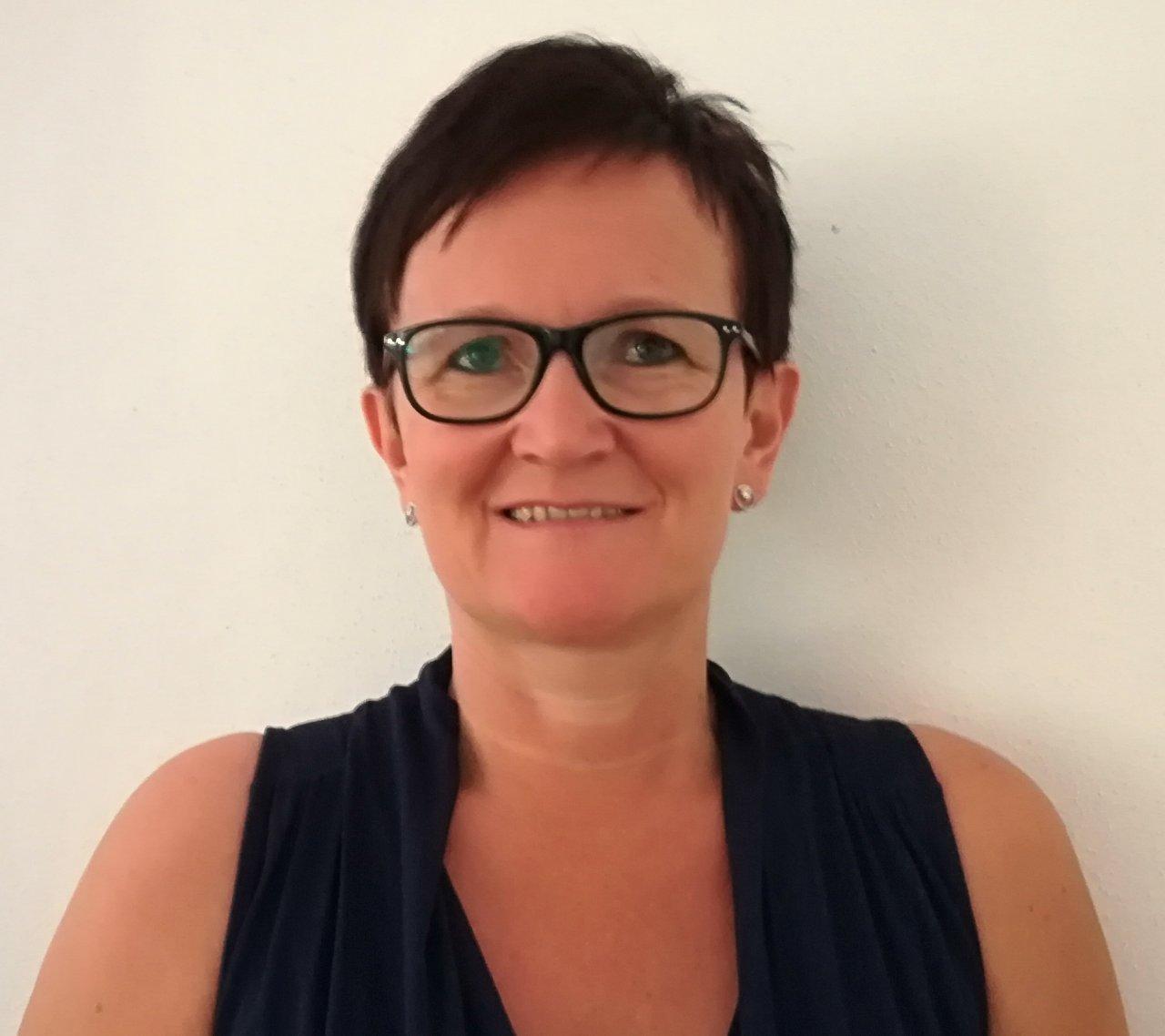 Das Bild zeit das Porträtfoto von Alexandra Pesendorfer mit kurzen schwarzen Haaren, einer schwarzen Brille und einem schwarzem Oberteil.