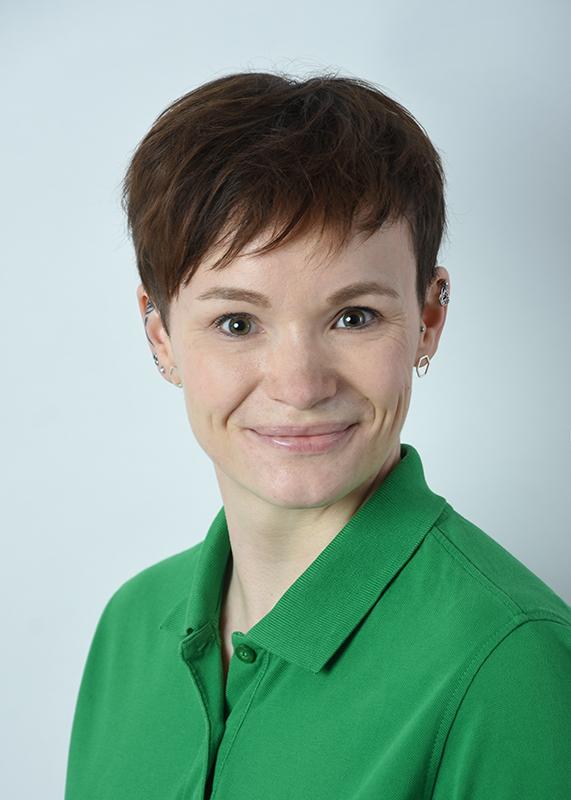 Das Portraitfoto zeigt Alexandra Kleinert aus Leipzig. Sie hat kurze braune Haare und trägt ein grünes Polo T-Shirt.