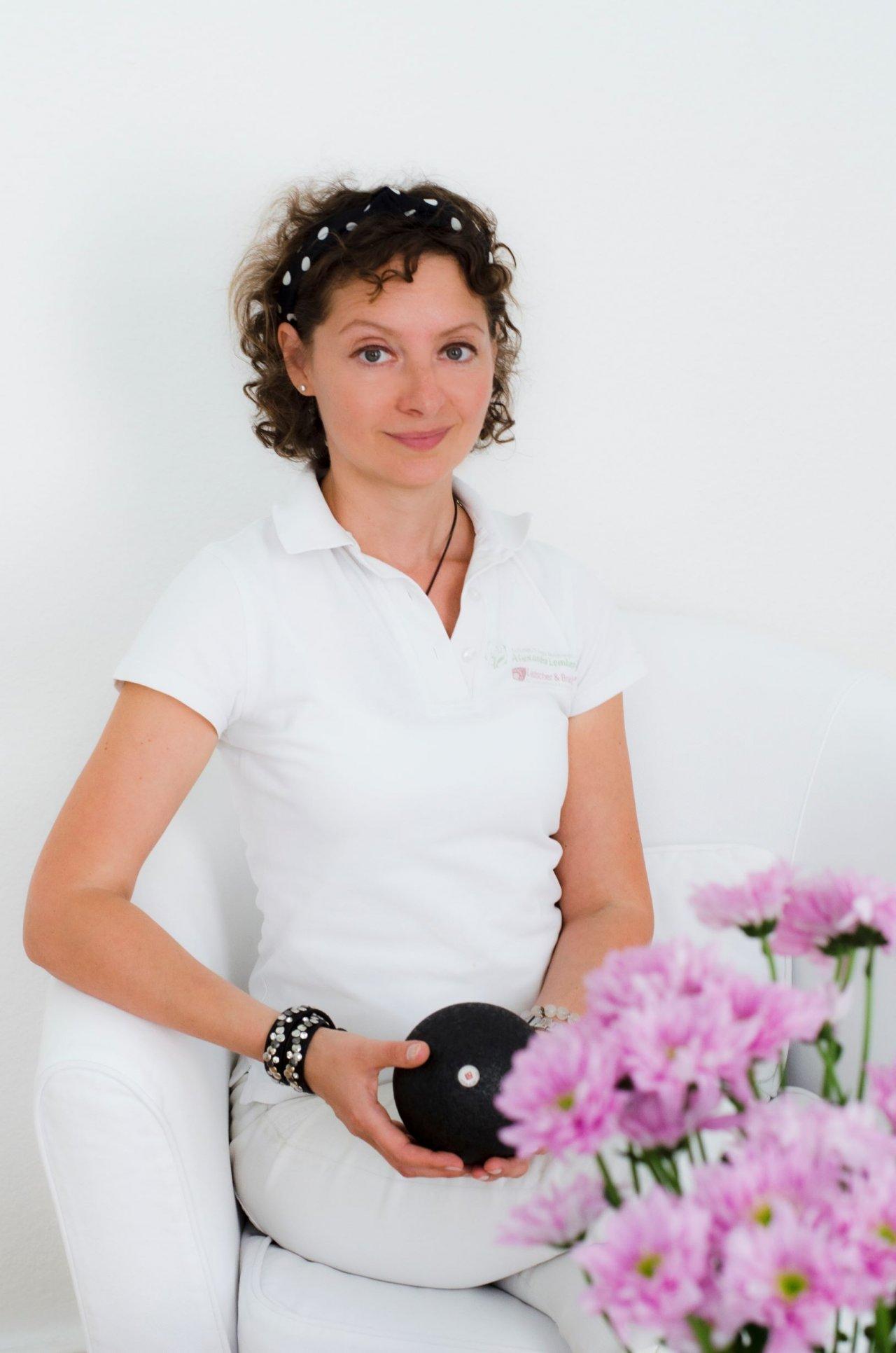 Auf dem Foto ist Alexandra Lemberg aus 40235 Düsseldorf zu sehen. Im Hintergrund sind bunte Motive zu erkennen. Sie hat braune wellige Haare, die sie als Zopf trägt. Auf dem Foto trägt sie eine silberne Kette mit einem Anhänger und ein weißes Polo T-Shirt