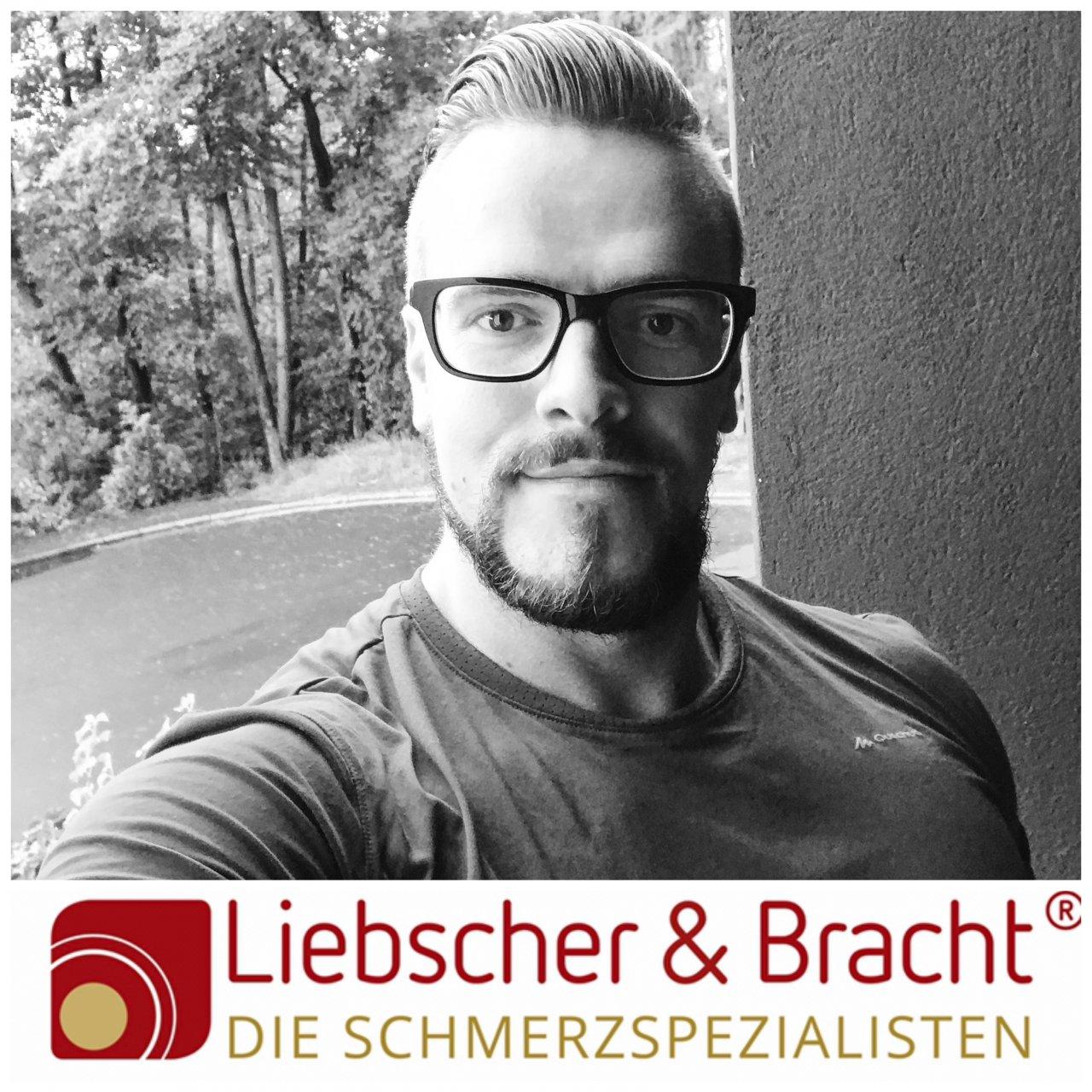 Das Selfie von André Kloos zeigt ihn vor einem Hintergrund mit Bäumen. Das Foto ist schwarz- weiß. André hat kurze Haare und trägt eine eckige dunkle Brille sowie einen Bart.