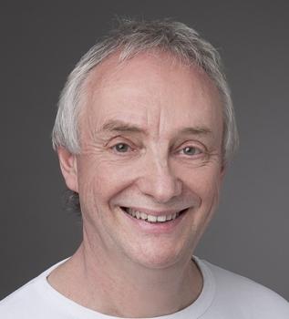 Der Schmerztherapeut aus Roggwil, André Henzmann hat hellgraue Haare und trägt ein weißes T-Shirt. Das Portraitfoto ist vor einem grauen Hintergrund aufgenommen worden.