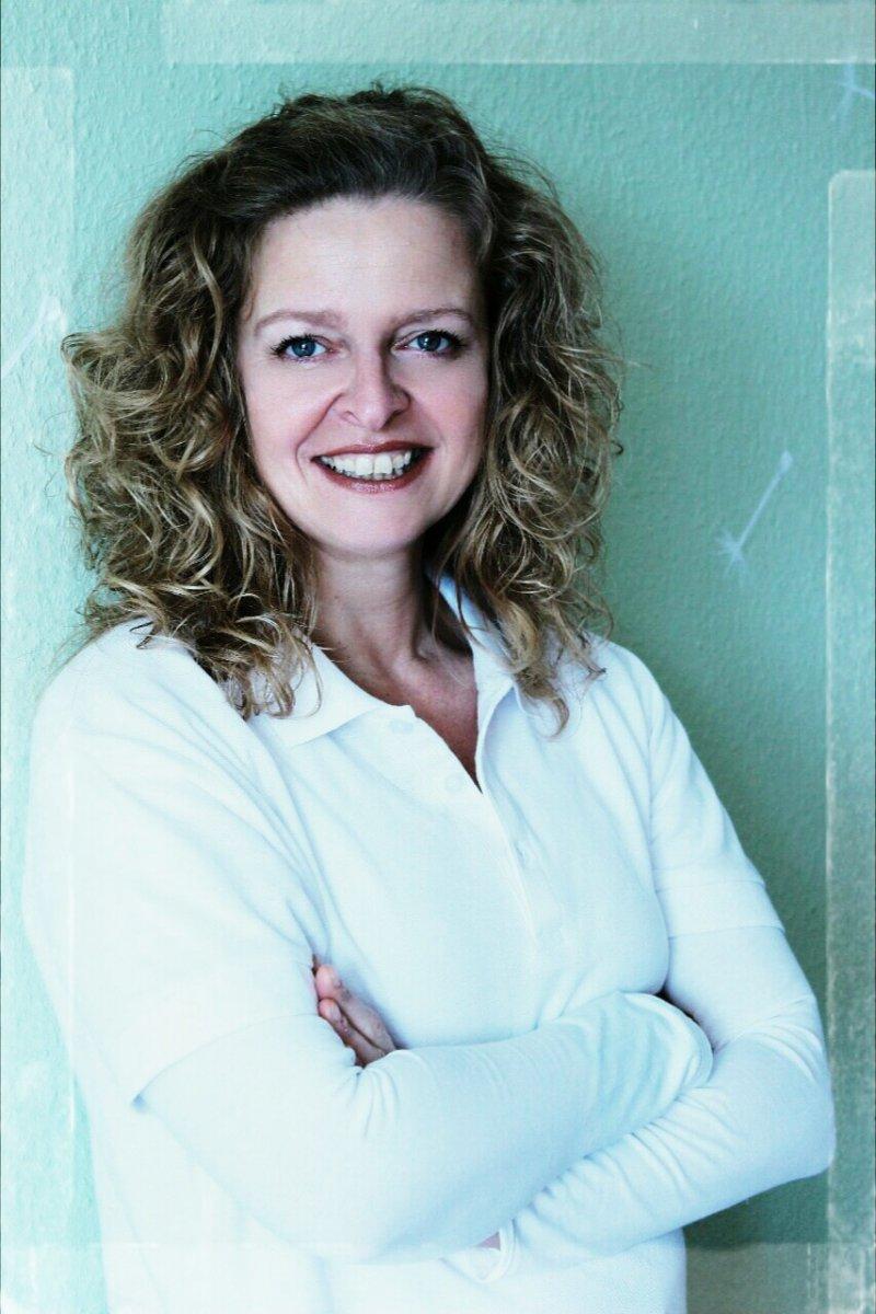 Das Foto zeigt Andrea Pape aus Wetter a. d. Ruhr. Sie steht an einer türkisfarbenen Wand. Sie hat schulterlange dunkelblonde Locken und trägt eine weiße Bluse. Sie hat die Hände vor den Armen verschränkt und lächelt in die Kamera.