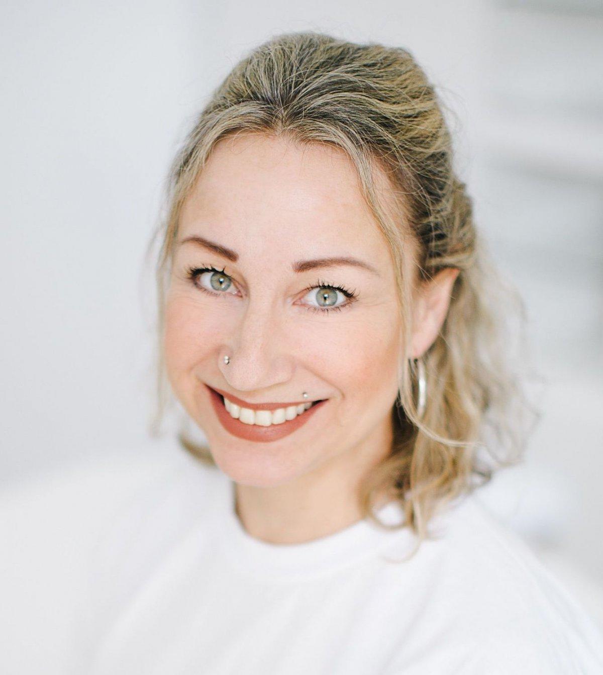 Das Foto zeigt Andrea Wernli aus Dübendorf vor einem weißen Hintergrund. Sie hat dunkelblonde Haare, die sie halb nach hinten gebunden hat. Sie trägt ein weißes T-Shirt und hat einen Nasenpiercing und auch einen an der Oberlippe. Auf dem Foto lächelt sie