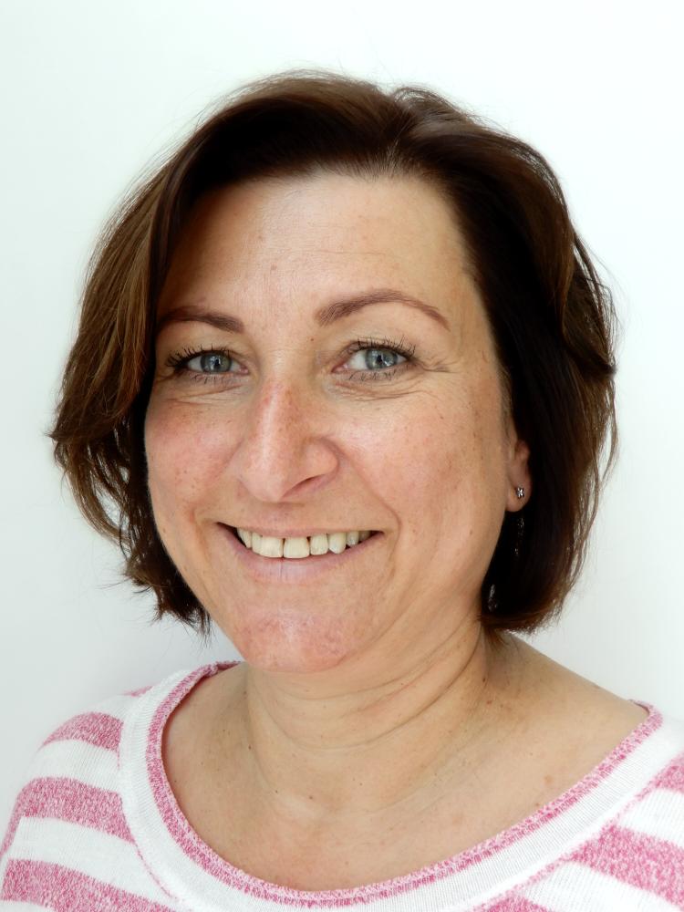 Auf dem Foto ist die Heilpraktikerin Anette Wehner aus Berlin. Sie hat kinnlange braune Haare und einen schrägen Pony. Auf dem Foto steht sie vor einem weißen Hintergrund und trägt ein weiß-rosa gestreiftes T-Shirt.