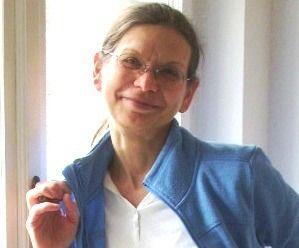 Auf dem Foto ist Angela Dzaack vor einem hellen Hintergrund zu sehen. Ihre langen braunen Haare trägt sie als Zopf und eine rahmenlose Brille. Sie trägt ein weißes T-Shirt und eine hellblaue Strickjacke.