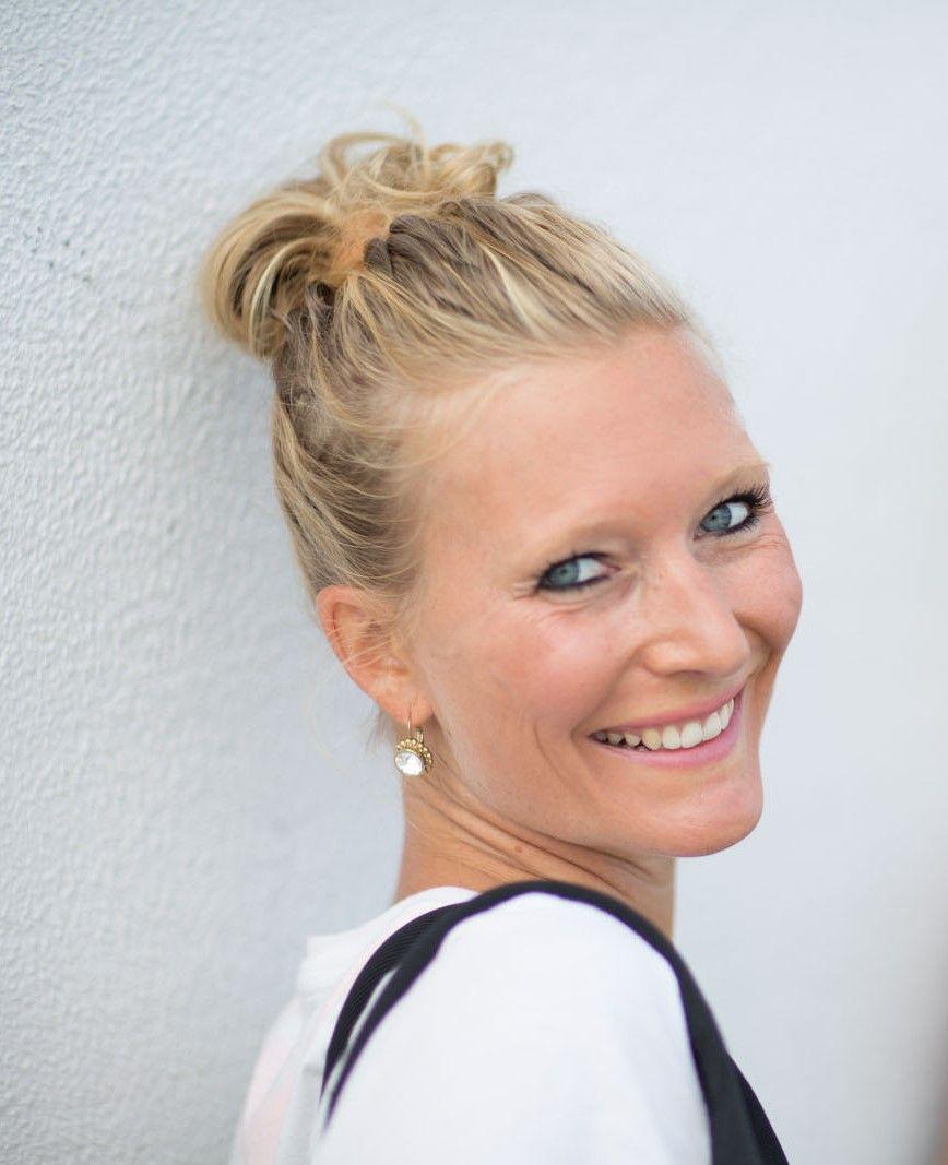 Auf dem Foto schaut Anja Kropfelder aus Bamberg schräg über ihre Schulter lächelnd in die Kamera. Sie hat lange blonde Haare, die sie als Top trägt. Sie hat ein weißes T-Shirt und silberne Hängeohrringe an.