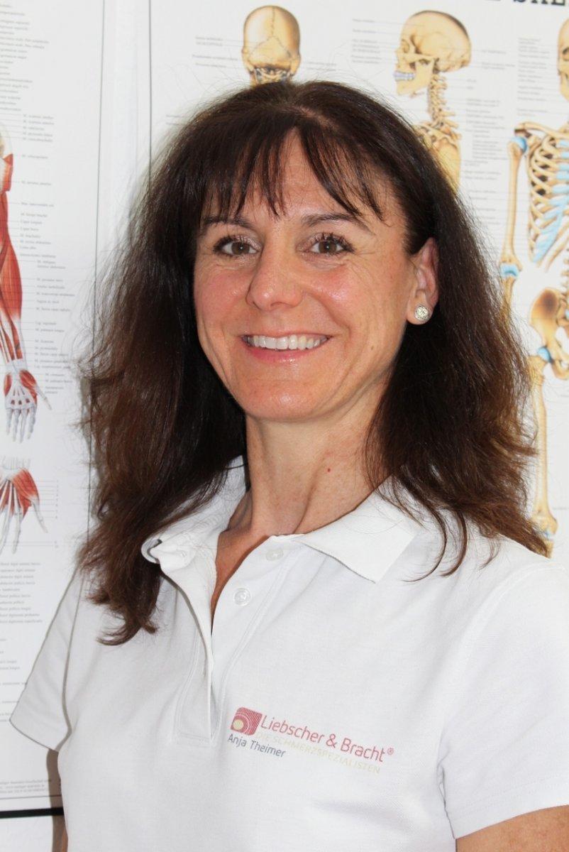 Anja Theimer, Physiotherapeutin und sktorale Heilpraktikerin aus Ladenburg steht vor Anatomie Plakaten. Sie hat lange wellige braune Haare mit Pony. Zudem trägt sie ein weißes Liebscher & Bracht Polo T-Shirt.