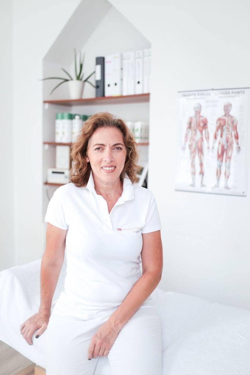 Auf dem Foto ist die Schmerzspezialistin Anna Dederer aus Schwäbisch Gmünd zu sehen. Sie sitzt auf einer Behandlungsliege und im Hintergrund sieht man ein Poster und ein Regal mit Ordnern und einer Pflanze. Sie hat mittellange braune Haare mit Locken. Sie