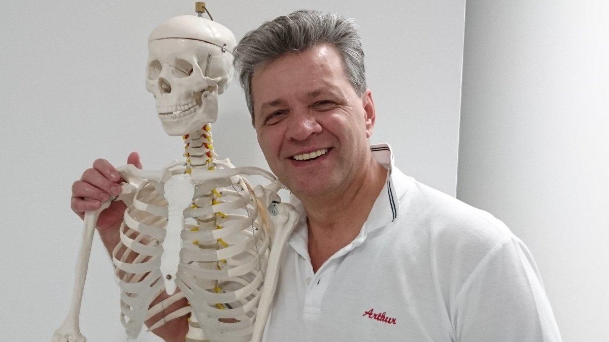 Der aus Heilbronn stammende Arthur Petruschin steht lachend mit einem Skelett im Arm vor einem weißen Hintergrund. Er hat kurze graue Haare und trägt ein weißes Polo T-Shirt.