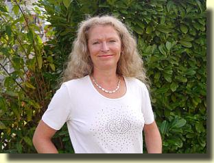 Auf dem Foto ist Bärbel Battenberg aus Duisburg vor einem grünen Busch zu sehen. Sie hat lange hellblonde Haare, die sich kräuseln und wellen. Auf dem Bild trägt sie eine silberne Kette und ein weißes T-Shirt.