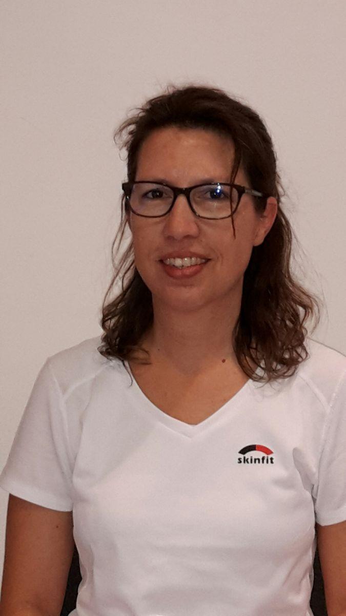 Das Foto zeigt Barbara Krähenbühl vor einem weißen Hintergrund. Sie hat schulterlange braune Haare, die sich leicht wellen und trägt eine eckige dunkle Brille sowie ein weißes T-Shirt mit Aufschrift.