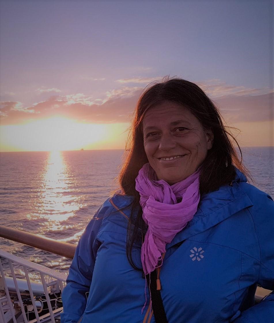 Das Foto zeigt die Physiotherapeutin Barbara Löffert. Im Hintergrund sieht man einen Sonnenuntergang vor einem Meer. Sie hat schulterlange braune Haare und trägt ein pinkes Tuch und eine blaue Jacke.