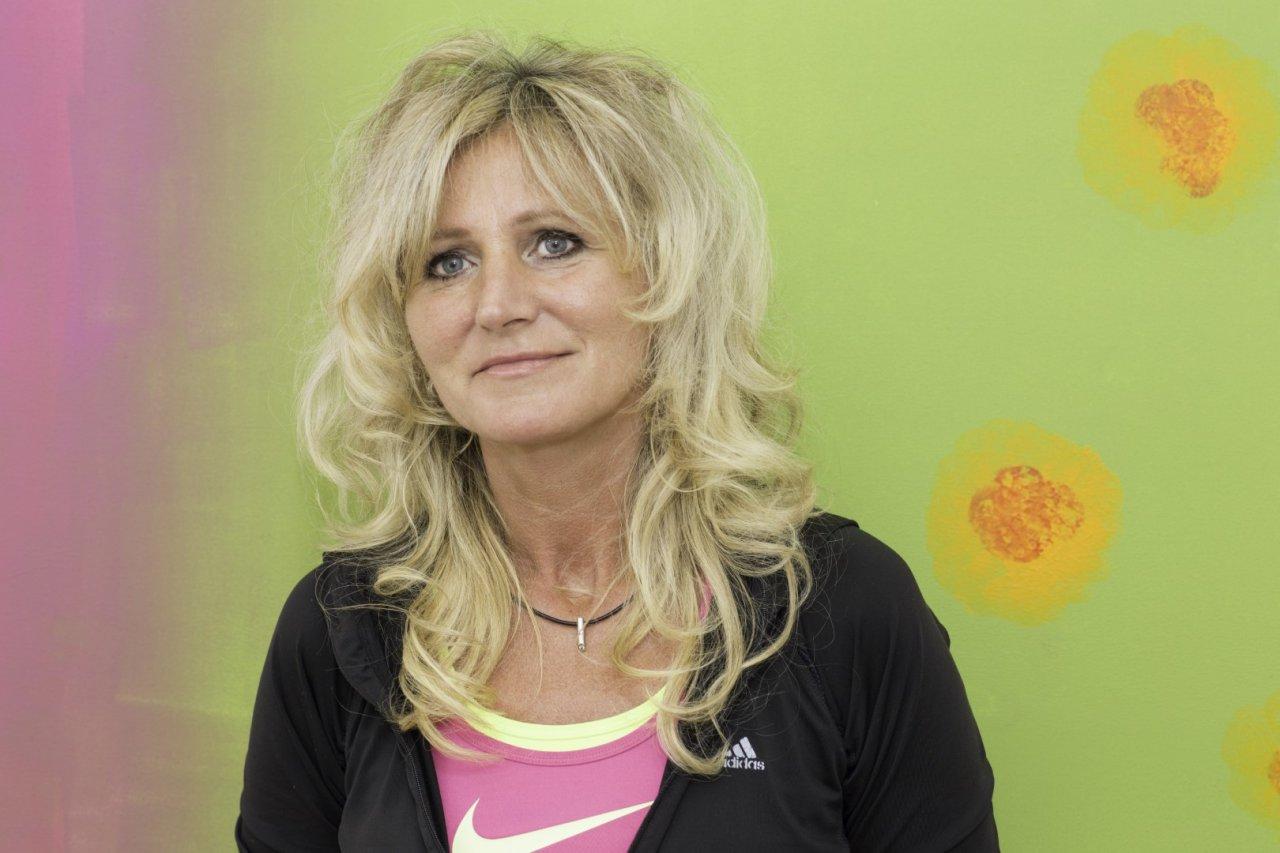 Auf dem Foto steht Beata Suhling vor einem grünlila Hintergrund. Sie hat lange blonde Haare, die sich wellen und locken, sowie einen Pony. Sie trägt eine schwarze Strickjacke und ein pinkes T-Shirt.
