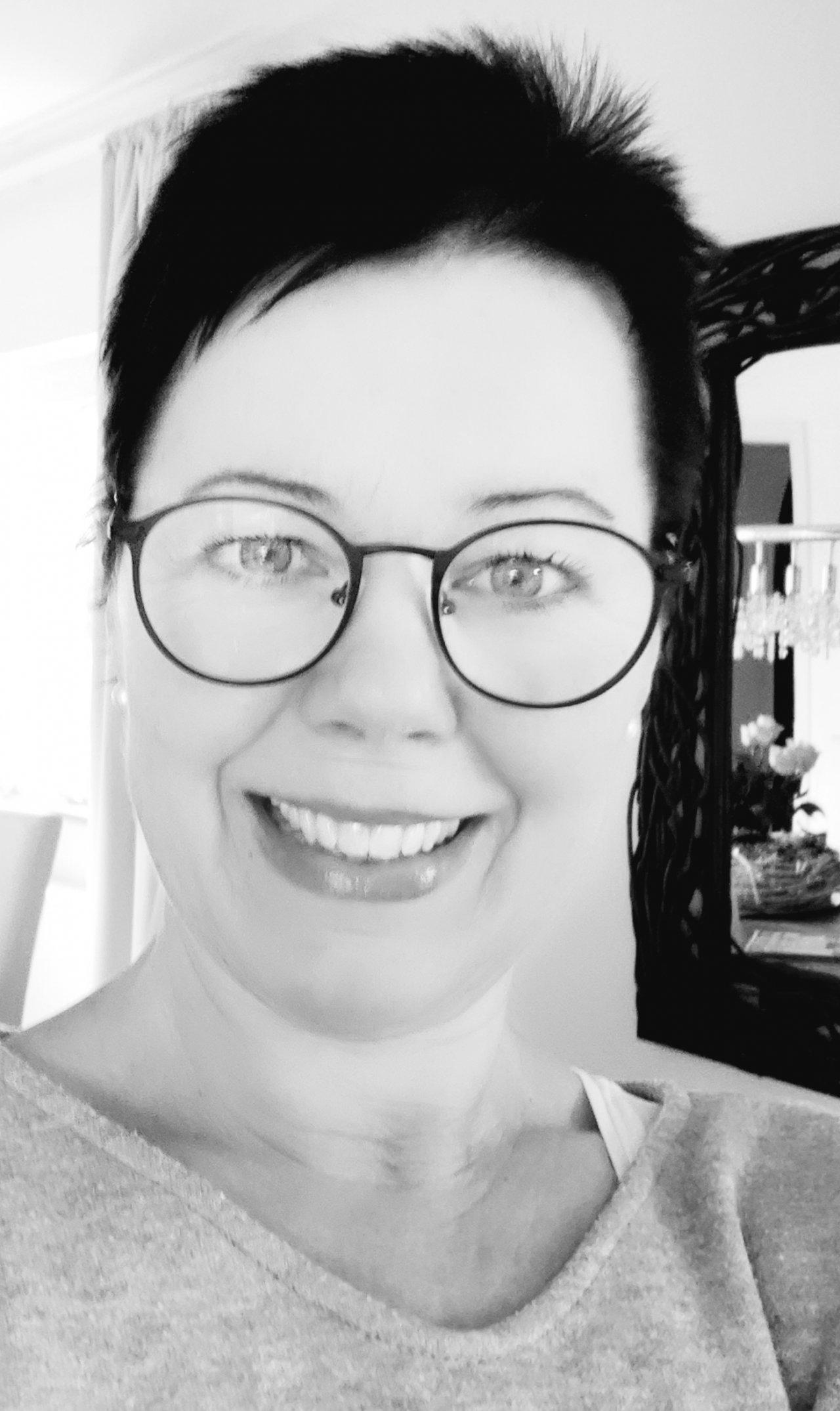 Auf dem schwarz-weiß Foto ist Beate Sandner aus Lollar zu sehen. Sie lächelt in die Kamera und trägt ein weißes T-Shirt. Außerdem hat sie kurze schwarze Haare.