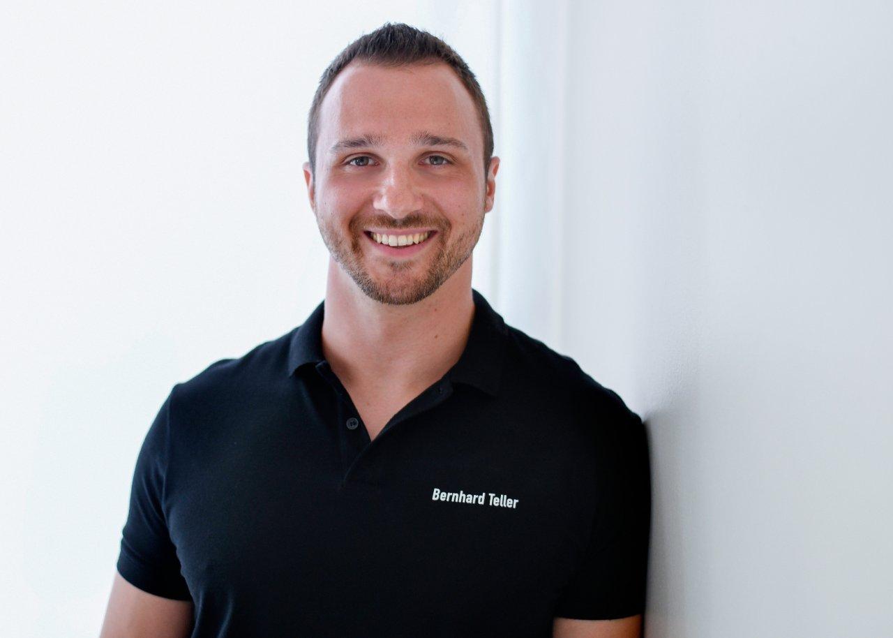 Das Bild zeigt den Schmerzspezialisten Bernhard Teller, der an einer weißen Wand lehnt. Er hat kurze braune Haare, einen Dreitagebart und ein schwarzes T-Shirt.