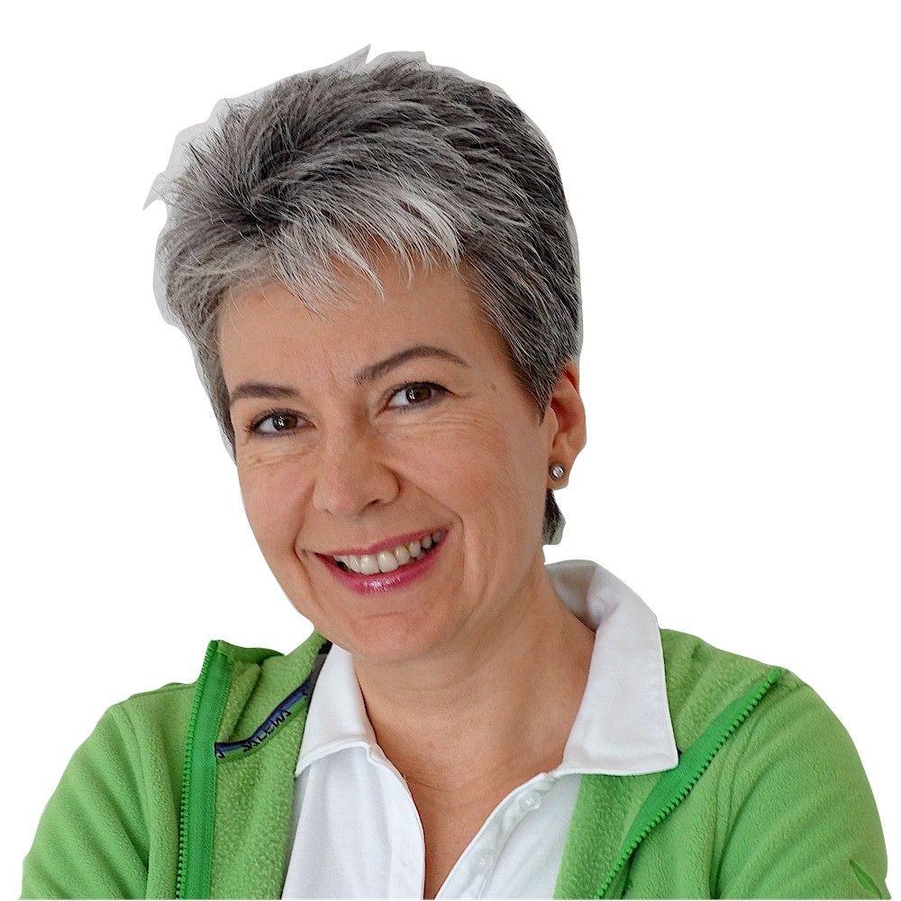 Bettina Mangold aus Stuttgart sieht man lachend vor einem weißen Hintergrund. Sie hat kurze schwarz graue Haare und trägt dazu ein weißes T-Shirt und eine grüne Strickjacke.