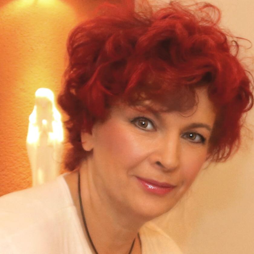 Das Foto zeigt die Masseurin Bettina Max aus Cottbus. Im Hintergrund steht eine helle Lampe vor einer orangefarbenen Wand. Sie hat kurze rote lockige Haare und trägt auf dem Foto ein weißes T-Shirt.