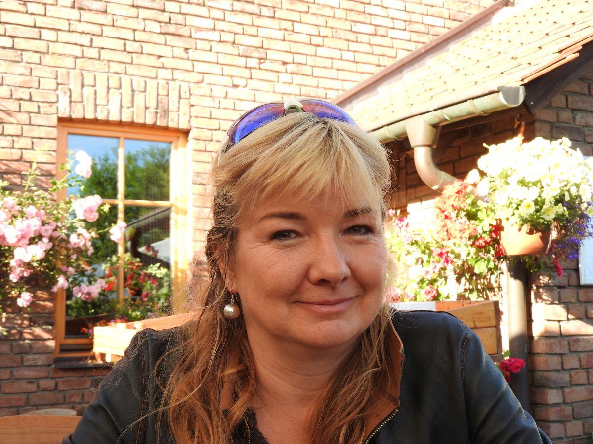 Das Foto zeigt Birgit Schröder aus Zehdenick OT Mildenberg vor einem Haus. Sie hat lange blonde Haare und trägt einen geraden Pony sowie eine Sonnenbrille auf dem Kopf. Sie trägt Ohrringe und eine dunkelgrüne Strickjacke.