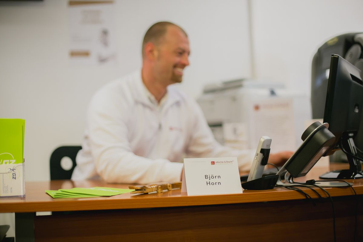Das Foto zeigt Björn Horn hinter seinem Schreibtisch. Er hat kurzes braunes Haar und trägt einen weißen Pullover. Der Fokus des Bildes liegt auf dem Namensschild, Björn Horn und der Hintergrund sind verschwommen.