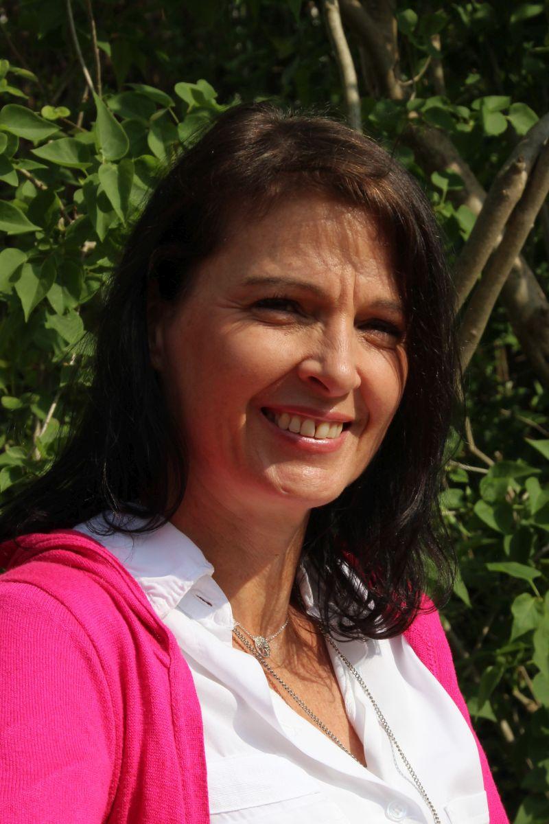 Auf dem Foto ist Birgit von Strenge vor einem grünen Naturhintergrund zu sehen. Sie hat braune schulterlange Haare und trägt eine weiße Bluse und darüber eine pinke Strickjacke. Sie steht leicht schräg und lacht in die Kamera.