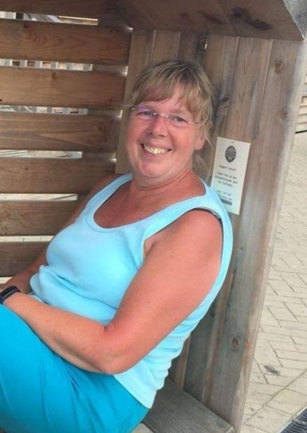 Auf dem Foto sitzt Britta Kriese auf einer Holzbank, mit Wänden, die man im Hintergrund auch sieht. Sie trägt ihre dunkelblonden Haare als Zopf und einen geraden Pony sowie eine rahmenlose Brille. Sie trägt ein hellblaues Top und eine türkisfarbene Hose.