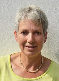 Brunhilde Dornieden aus 51789 Lindlar steht vor einer weißen Wand. Sie hat kurze graue Haare und trägt ein gelbes T-Shirt und eine Perlenkette.