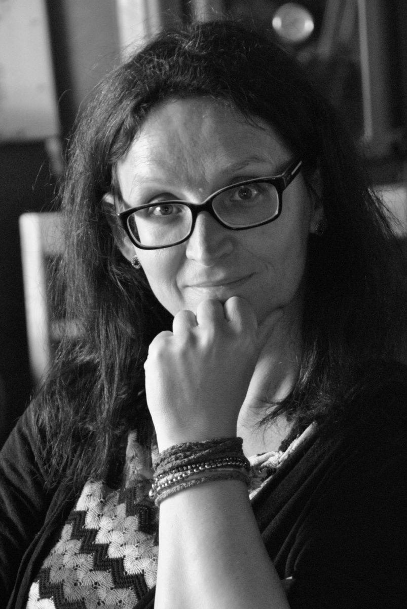 Das schwarz-weiß Foto zeigt Carina Schäfer-Sowinski aus 56564 Neuwied. Sie hat eine Hand an ihr Kinn gelegt und schaut freundlich in die Kamera. Sie hat lange dunkle Haare und eine eckige Brille.