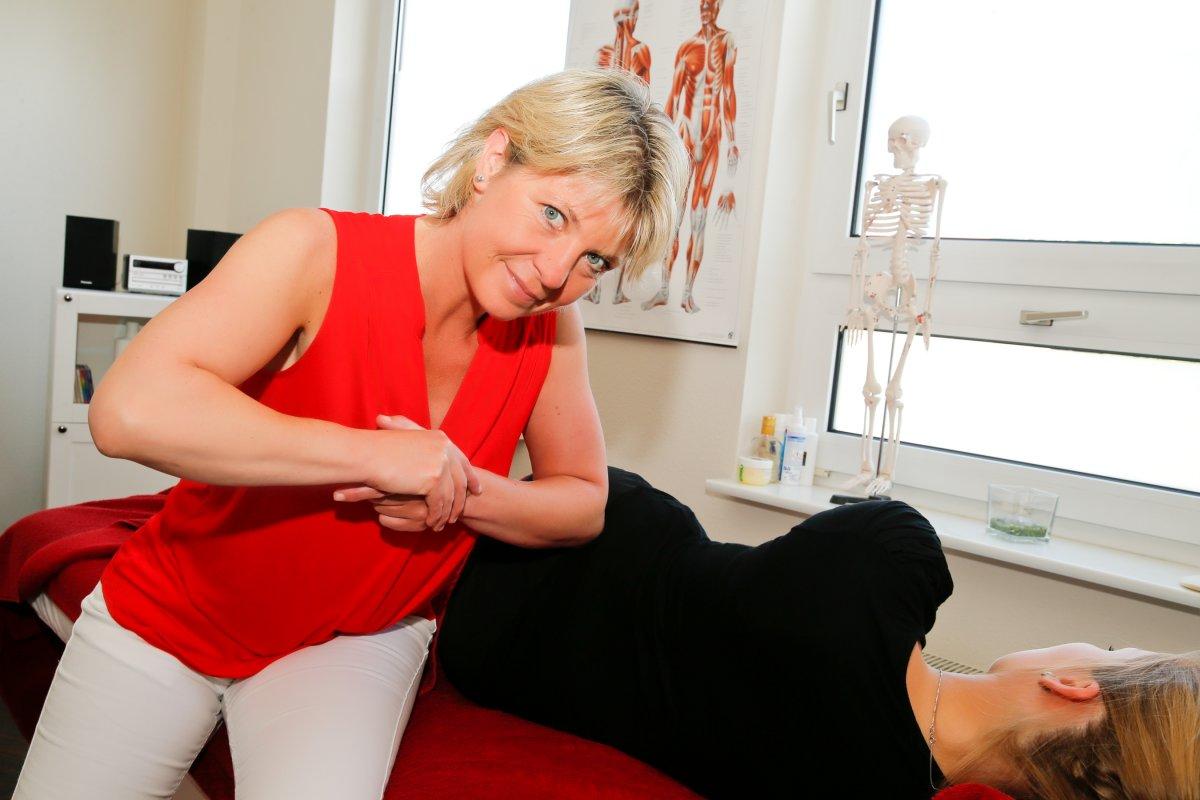 Das Foto zeigt die Physiotherapeutin Carola Busse, wie sie einen Patienten behandelt. Dieser liegt mit dem Rücken zur Kamera und Frau Busse sitzt davor und drückt mit ihrem Ellenbogen in den Rücken des Patienten. Frau Busse hat kinnlange blonde Haare und