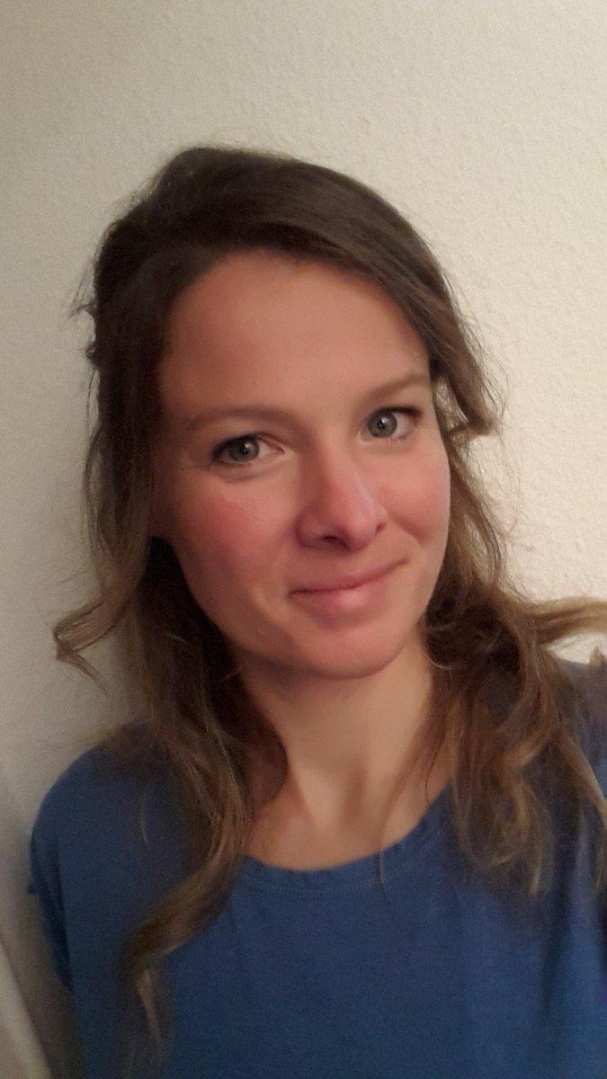 Auf dem Foto schaut Carolin Kaiser aus Pforzheim freundlich in die Kamera. Sie hat lange braune Haare, die sich leicht locken und trägt ein blaues T-Shirt.