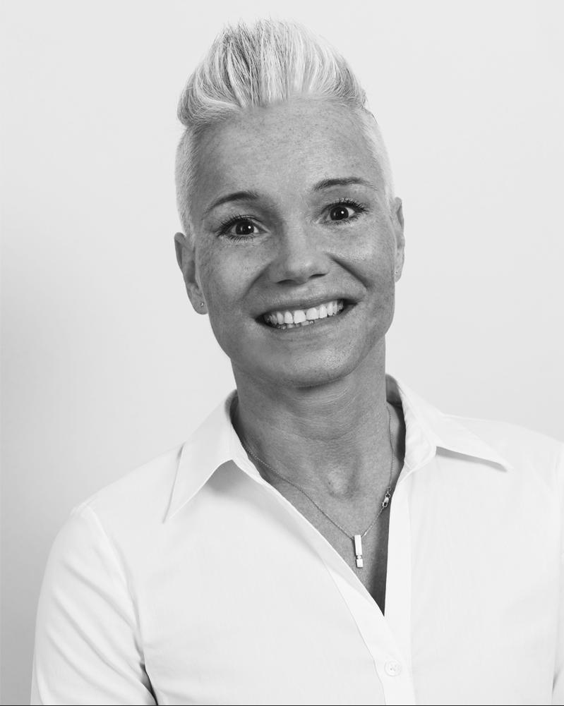 Das schwarz-weiße Portraitfoto von Cathrin Theissen aus Dittelbrunn zeigt Physiotherapeutin Cathrin Theissen sympathisch lächelnd. Sie hat kurze helle Haare und trägt eine helle Bluse.