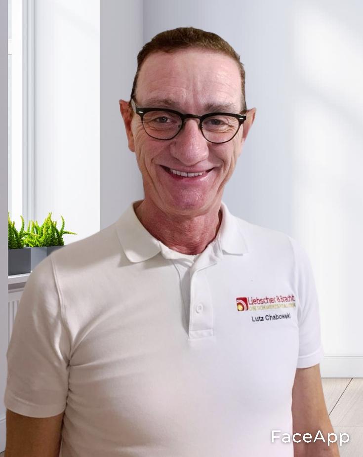 Lutz Chabowski hat kurze braune haare und eine schwarze Brille. Im Hintergrund des Therapeuten aus Erlangen befindet sich ein Raum mit Menschen.