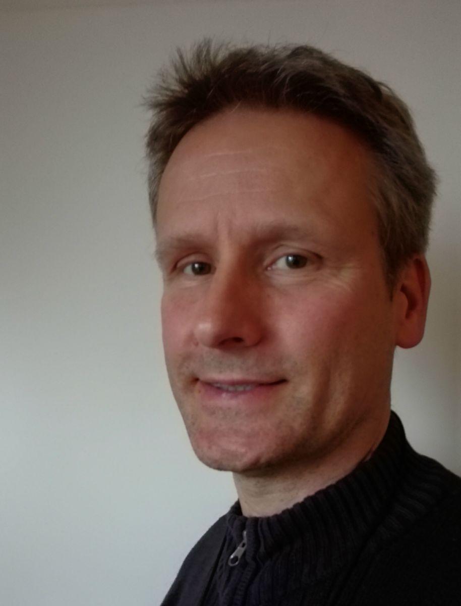 Auf dem Foto ist der Physiotherapeut Christian Bellebaum aus Siegen zu sehen. Er steht vor einem hellgrauen Hintergrund und hat kurzes dunkelblondes Haar. Dazu trägt er eine schwarze Strickjacke.