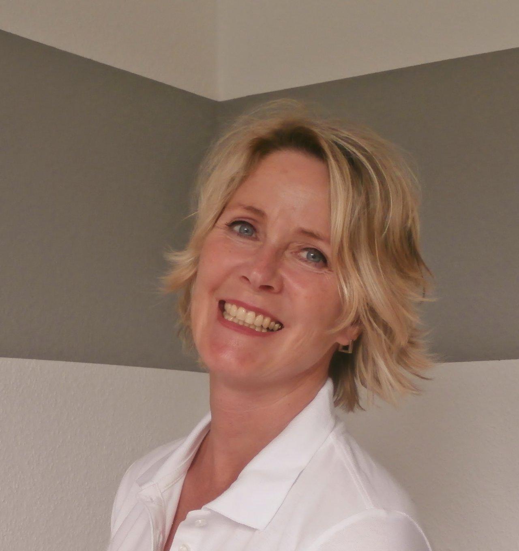 Christiane Lansnicker aus Celle steht vor einem weißen Hintergrund mit einem grauen Band. Sie lacht in die Kamera und steht schräg. Ihre Haare sind blond und kinnlang und sie trägt ein weißes Polo T-Shirt.