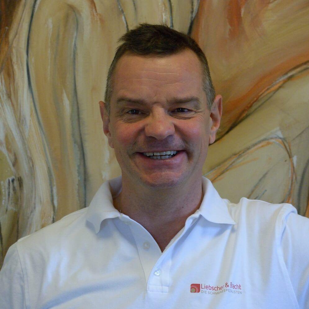Das Foto zeigt den Physiotherapeuten Christoph Juhrte, welcher vor einem bunten Hintergrund steht. Er hat kurze dunkle Haare und trägt ein weißes Liebscher & Bracht Polo T-Shirt.