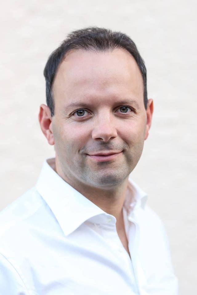 Christoph Schedler ist in Garmisch-Partenkirchen Physiotherapeut und steht vor einer hellen Wand. Er hat kurze dunkle Haare und trägt ein weißes Hemd.