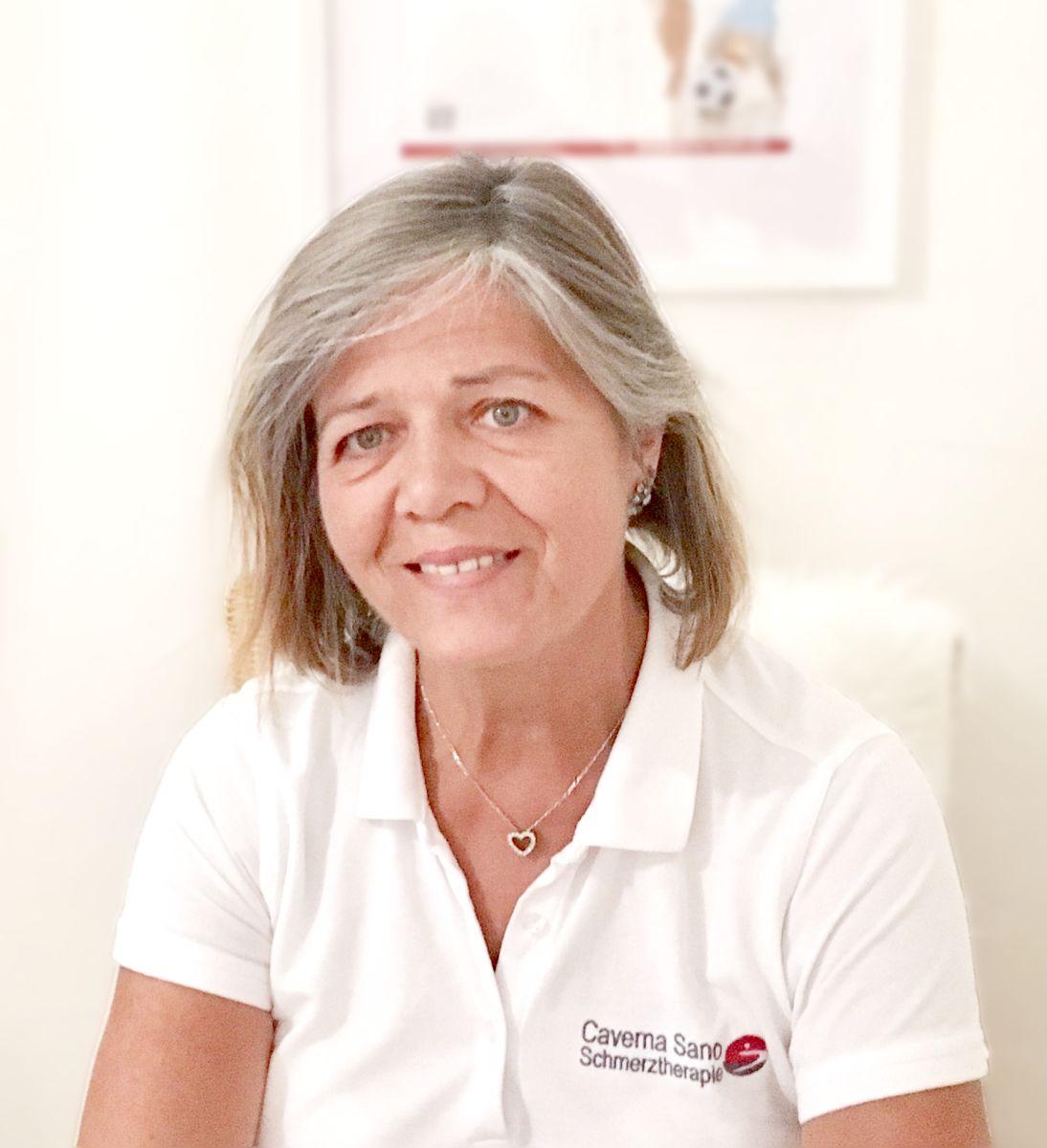 Claudie Klein hat mittellange grau-braune Haare und sitzt vor einem hellen Hintergrund mit einem Poster. Sie trägt ein weißes Polo T-Shirt und eine silberne Kette.