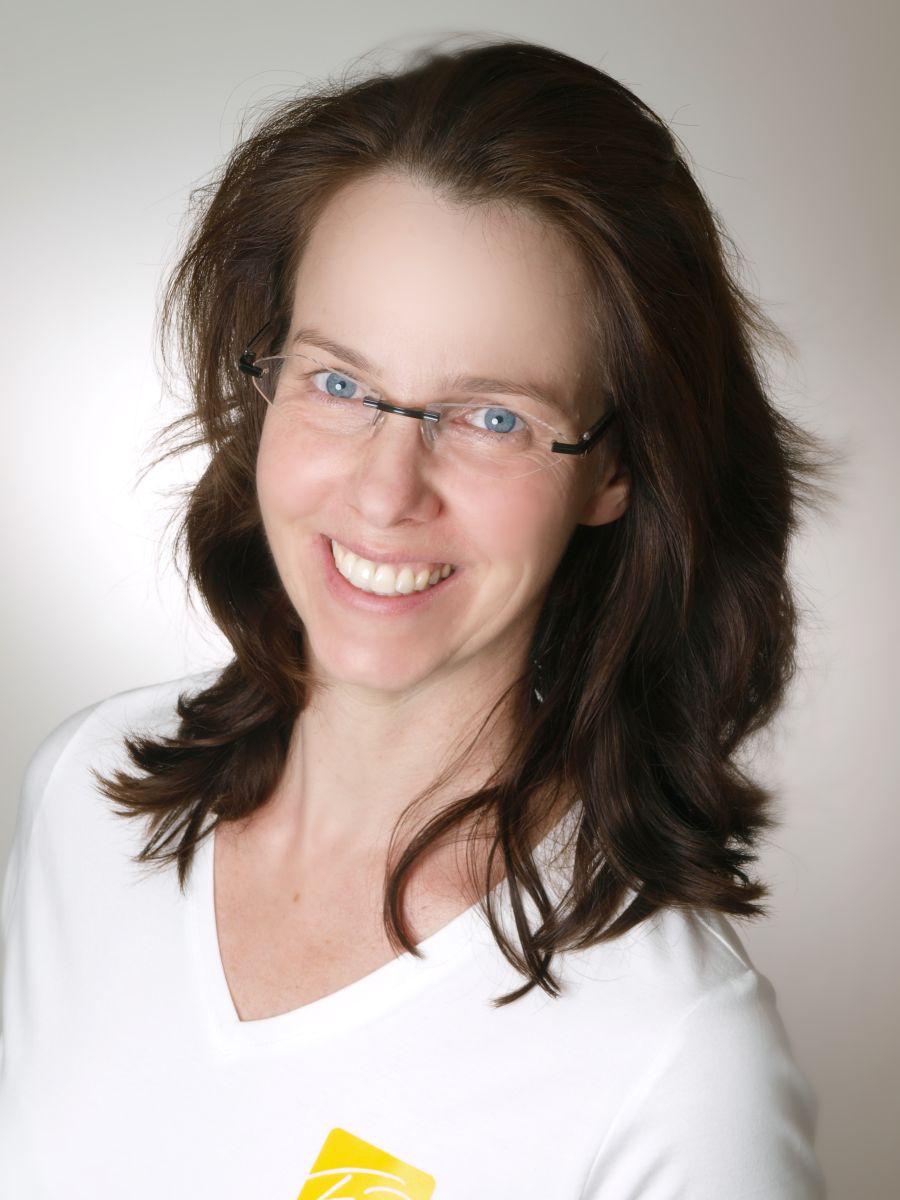 Die aus Kassel stammende Claudie Koch-Remmele wurde vor einem hellen Hintergrund fotografiert. Sie hat schulterlange braune Haare und trägt eine rahmenlose Brille. Auf dem Foto lächelt sie in die Kamera und trägt ein weißes T-Shirt.