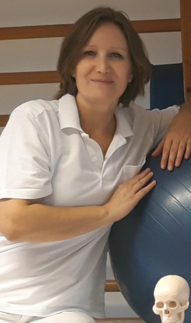Das Foto zeigt Claudia Pfeffer neben einem Gymnastikball. In der rechten unteren Ecke sieht man einen Kopf von einem Modellskelett. Sie lehnt gegen den Gymnastikball mit ihrer linken Seite. Auf dem Foto hat sie kinnlanges braunes Haar und ein weißes Polo