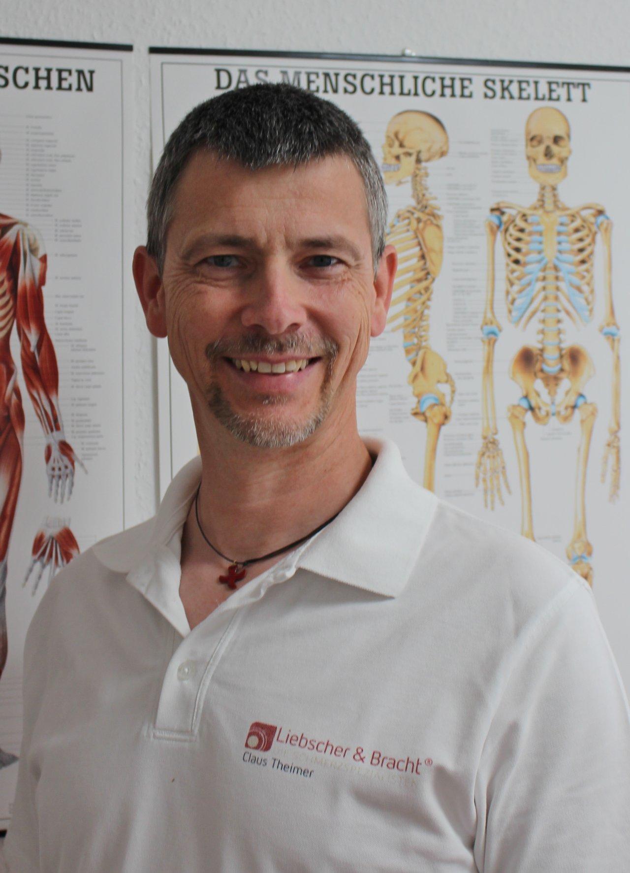 Claus Theimer aus 68526 Ladenburg steht vor einem Plakat des menschlichen Skeletts. Er hat schwarzgraue Haare und einen Bart. Auf dem Foto lächelt er in die Kamera und trägt ein weißes Liebscher & Bracht Polo T-Shirt.