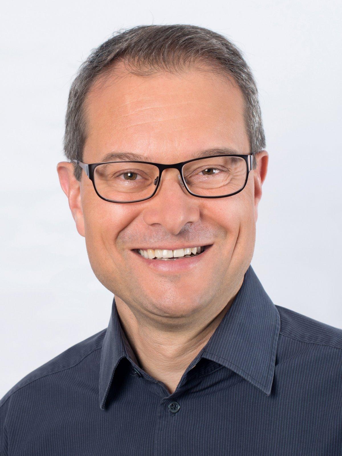 Auf dem Foto ist Cyril Kreyenbühl aus Zürich zu sehen. Er hat kurzes schwarz graues Haar und trägt eine eckige schwarze Brille sowie ein graues Hemd.