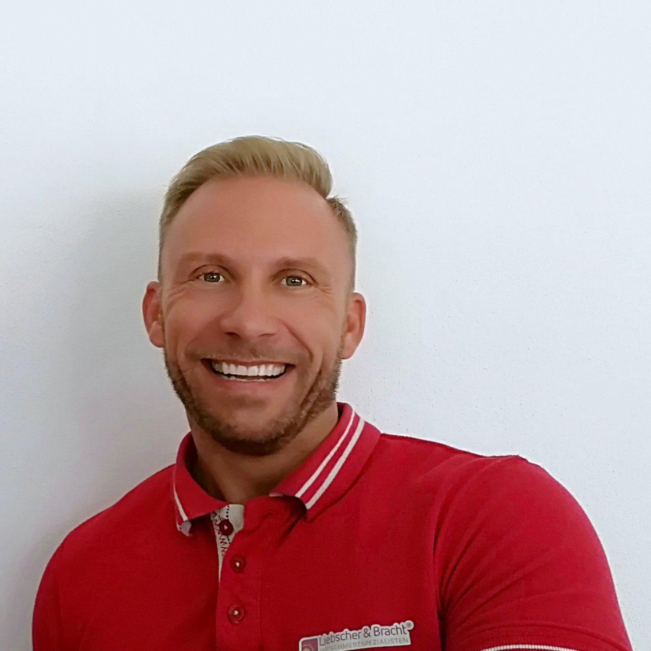Das Foto zeigt den Physiotherapeuten Daniel Nenz. Er hat kurze blonde Haare und trägt ein weißes Polo T-Shirt.