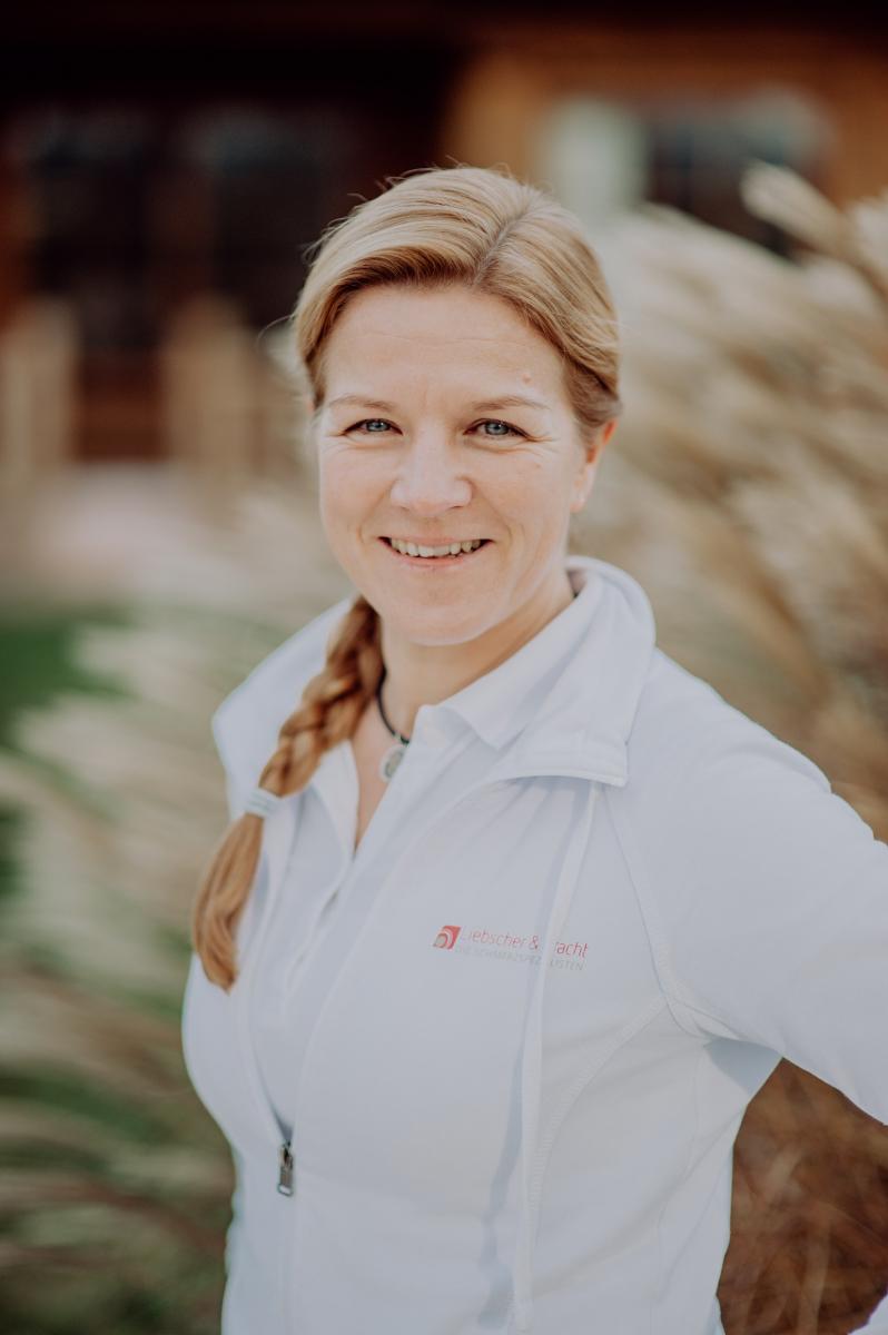 Das Oberkörperfoto zeigt Daniela Alterbaum aus Dötlingen. Sie steht vor einem hellbraunen Hintergrund. Ihre langen braunen Haare hat sie seitlich zu einem Zopf geflochten und lacht in die Kamera. Außerdem trägt sie eine weiße Liebscher & Bracht Strickjack