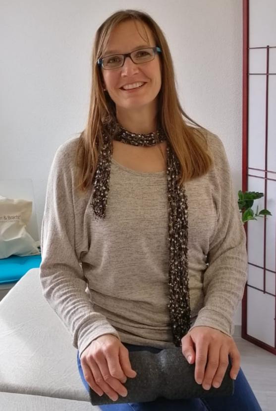Das Foto zeigt Daniela Steuri aus Wilen b. Will. Sie sitzt auf einer Behandlungsliege und hat in den Händen eine Faszienrolle, die über ihrem Bein liegt. Sie hat lange braune Haare und trägt eine eckige Brille. Steuri schaut lachend in die Kamera und träg